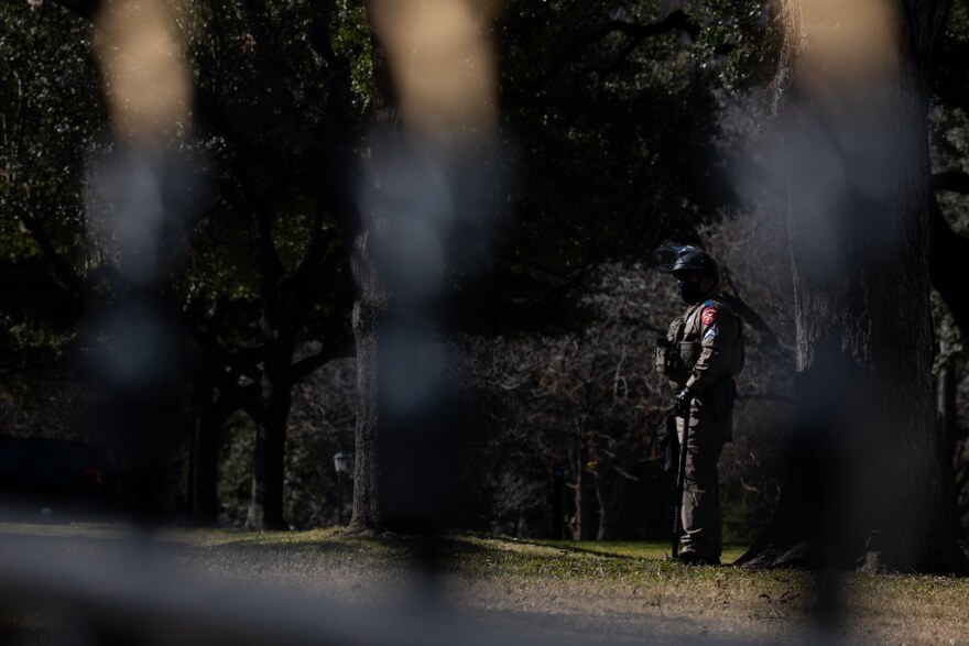 A law enforcement officer stands watch on the Capitol grounds Saturday after reports of planned events by violent extremists at state capitols across the U.S.