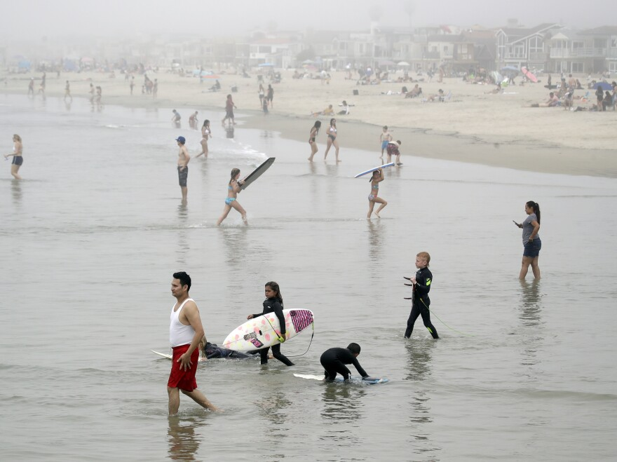 Crowds descend upon Newport Beach, Calif., last Sunday. Gov. Gavin Newsom warned that defiance of stay-at-home orders could put the state's progress in fighting the coronavirus at risk.