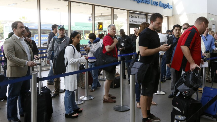 Travelers stand in line at Los Angeles International Airport on Monday. Congress moved quickly this week to give the Federal Aviation Administration flexibility to end air traffic controller furloughs that resulted in flight delays at several airports.