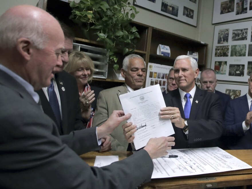 Vice President Pence files to list President Trump on the New Hampshire primary ballot to New Hampshire Secretary of State Bill Gardner (left) on Thursday in Concord, N.H.
