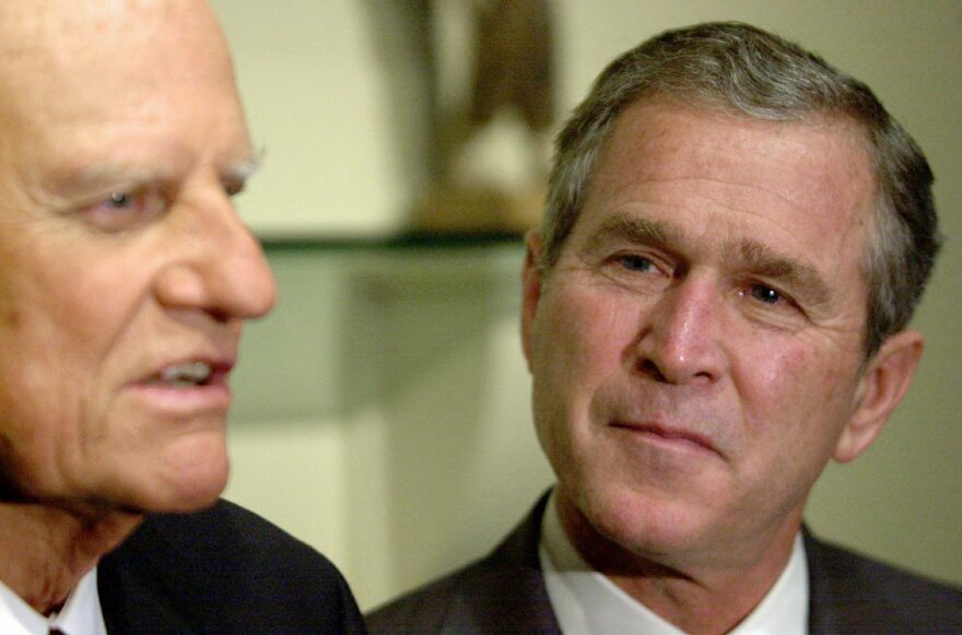 """George W. Bush, then as a Republican presidential candidate listens to the Rev. Billy Graham. Bush credits Graham with his """"born-again"""" breakthrough."""