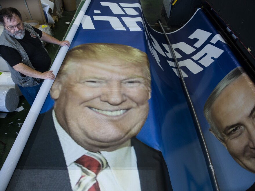 An employee works on a Likud party billboard showing Israeli Prime Minster Benjamin Netanyahu and President Trump in a printing house earlier this month in Rosh Haayin, Israel.