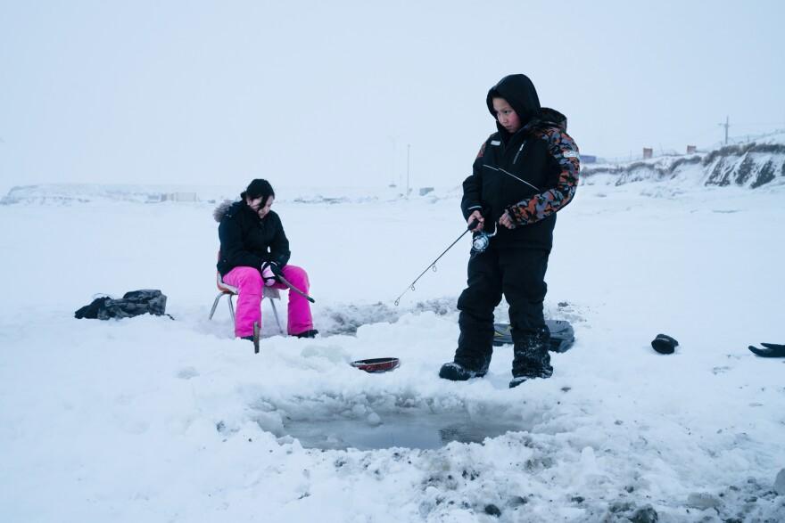 Joanna Woods, 12, (left) and her cousin Mick Chakuchin, 10, go ice fishing in Toksook Bay.