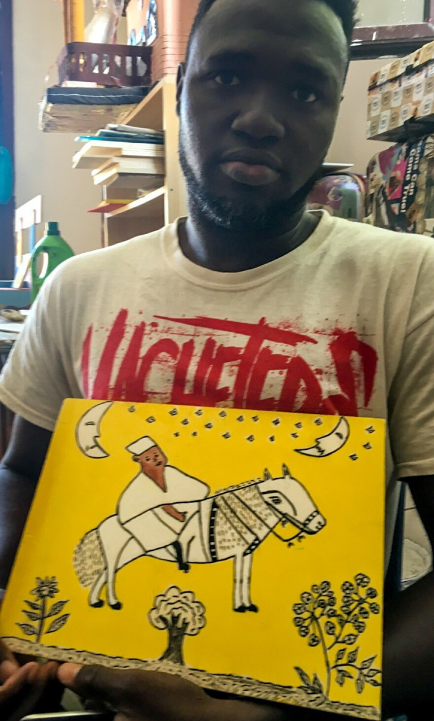 """Zacob Camara of Guinea with his Chagall-like depiction of an """"African hero."""""""