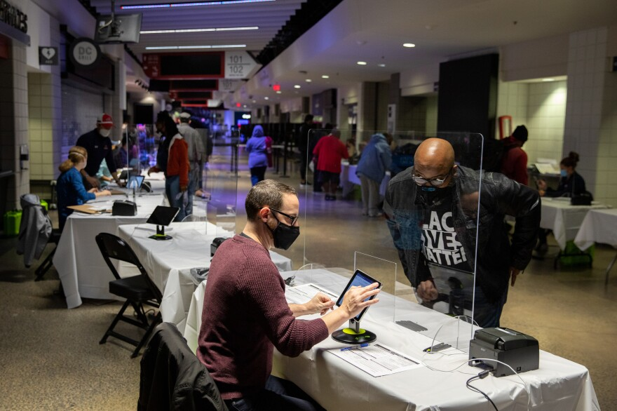 Brian Diem, left, checks in a voter on the first day of early voting at Capital One Arena in Washington, D.C., U.S., on Tuesday, October 27, 2020.