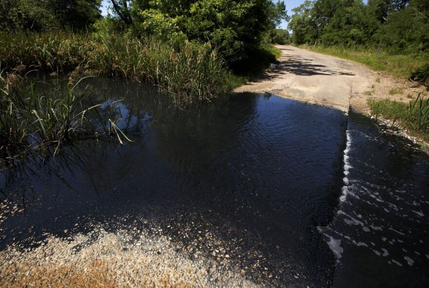 Skull Creek flows black as it crosses over a country road downstream from Inland Environmental & Remediation Inc. near Altair on April 14, 2019.