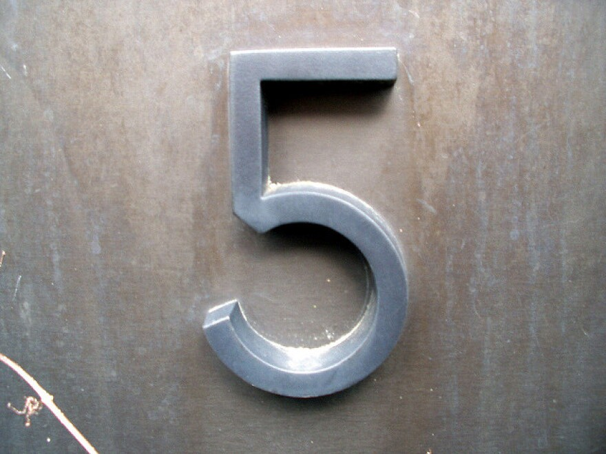 A silver number 5 on a grey background.
