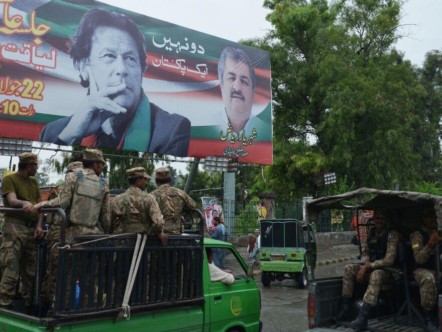 Pakistani soldiers patrol a street with a billboard featuring an image of Imran Khan in Rawalpindi.