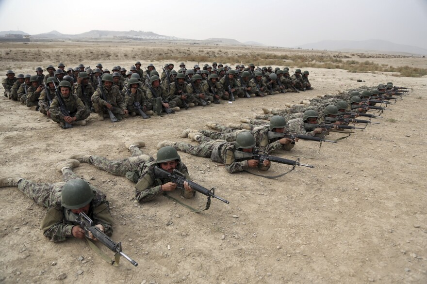 A group of Afghan National Army soldiers watch others participate in a live fire exercise at the Afghan Military Academy last October in Kabul, Afghanistan.