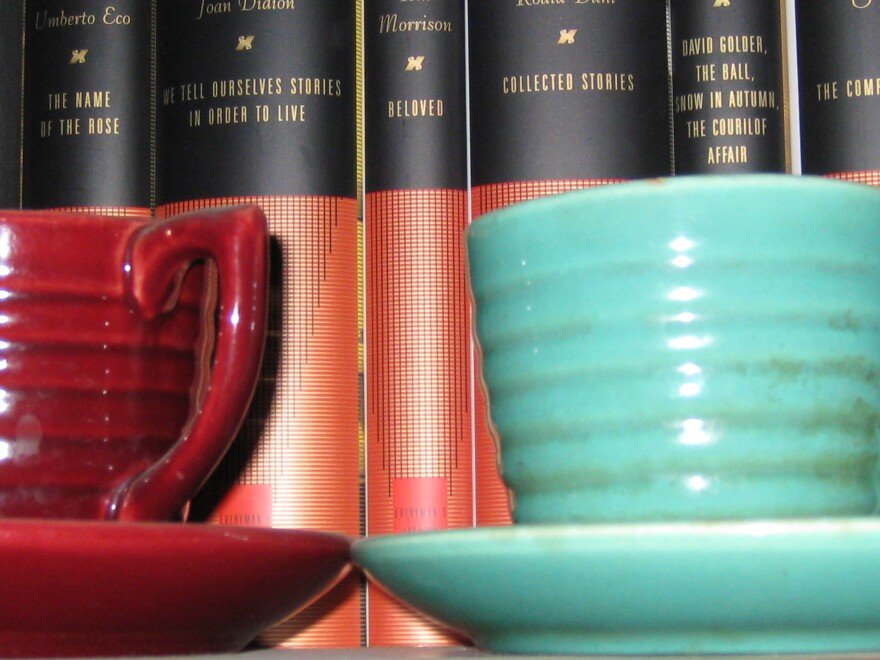 red and teal mugs sit in front of books