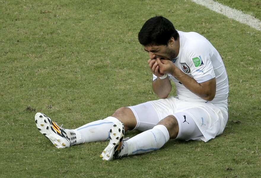 Uruguay's Luis Suarez sits on the pitch after apparently biting Italy's Giorgio Chiellini during a World Cup soccer match in Brazil on Tuesday.
