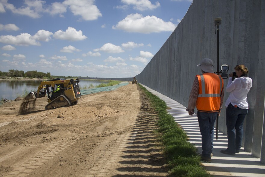Marianna Treviño-Wright and Hector Guajardo, a land surveyor, document the erosion and work being done at Fisher's private border wall