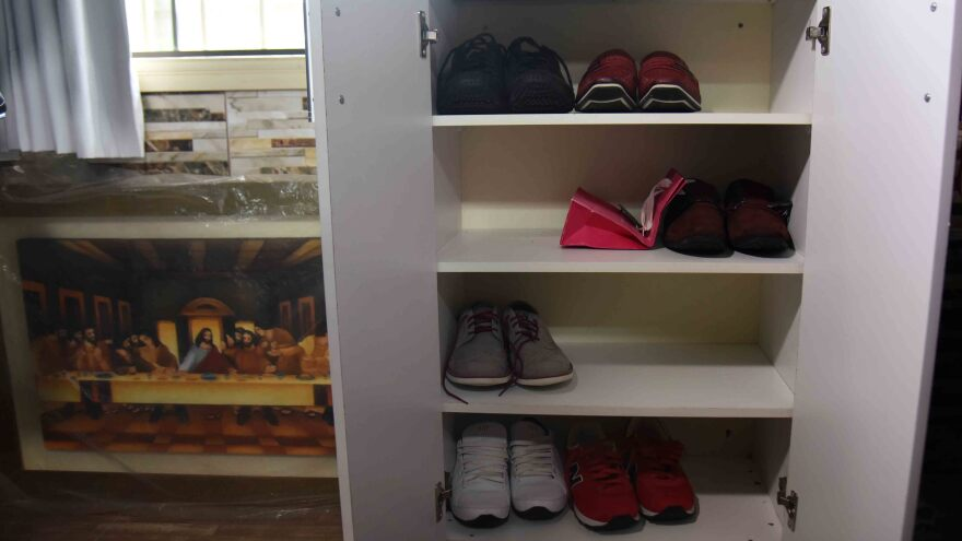Shoes, art and a tiled wall in Chimenes Pavao's prison quarters.