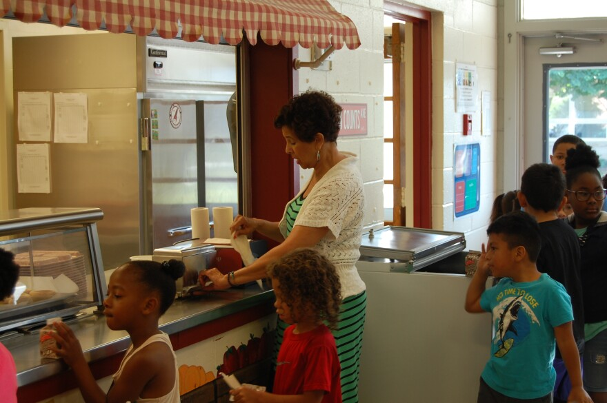 Debra Corbett helps students get their breakfast during a summer program in July 2018 called Rising Rockets at Ranson Elementary School.