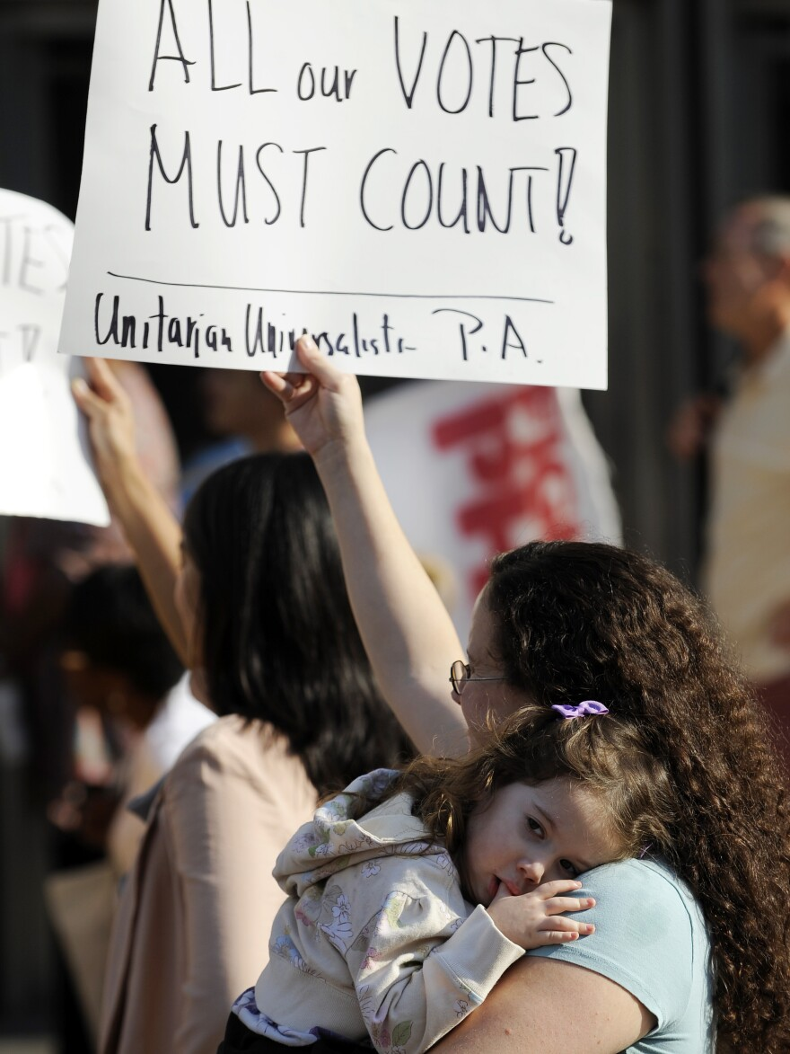 Emily Goldberg, with her daughter, Willa, 2, holds up a sign during the NAACP voter ID rally to protest against Pennsylvania's voter ID law on Sept. 13. Tuesday, a judge ordered that the law not be enforced in the Nov. 6 presidential election.