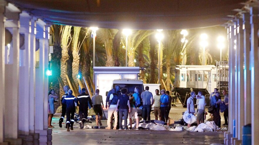 People stand next to covered bodies in the early hours of Friday on the Promenade des Anglais in Nice, southern France.