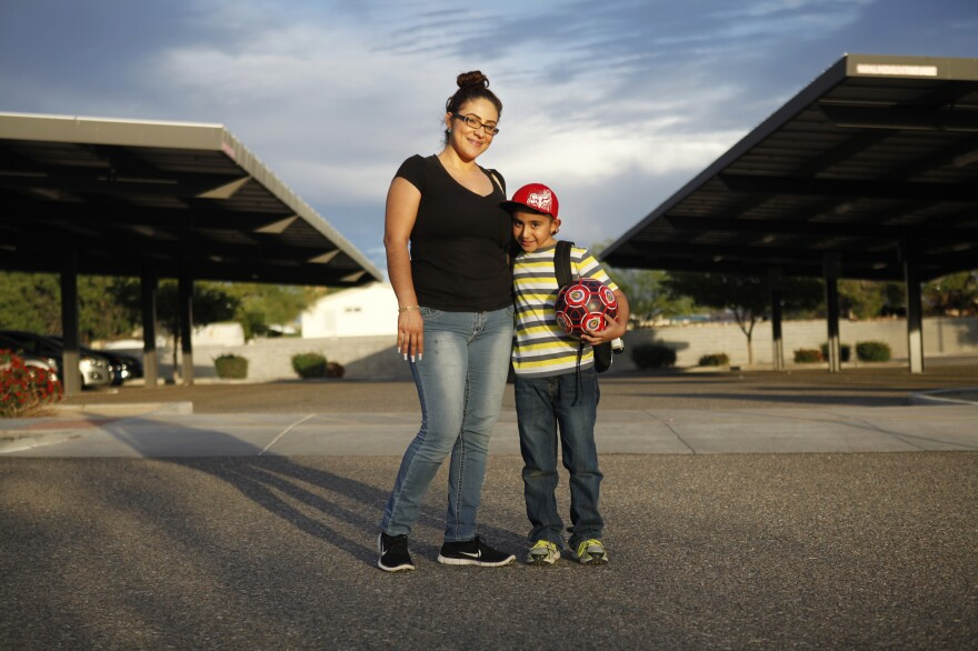 Humberto and his mother, Zaira Yanez, pose for a portrait outside his school. Not knowing english, she says, sometimes keeps her from helping Humberto more.