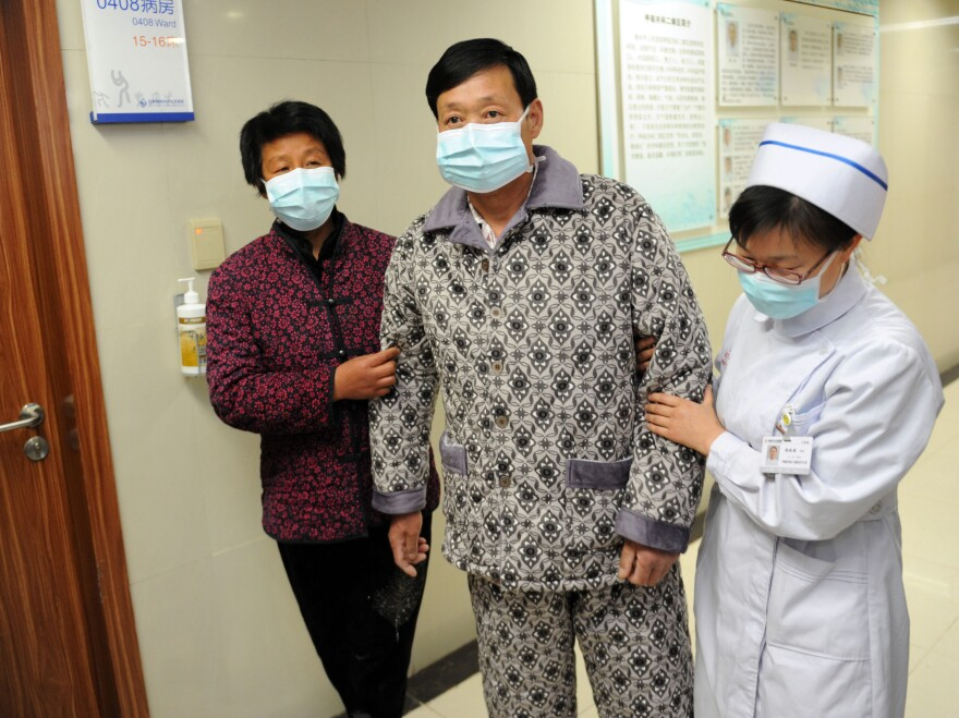 An H7N9 bird flu patient is escorted after his recovery and approval for discharge at a central China hospital on Friday.