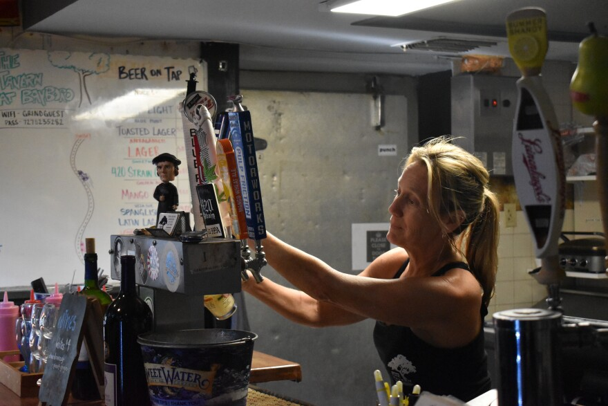 Woman pours a beer from the tap