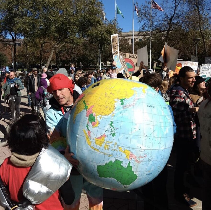 A climate protester holds an inflatable globe.