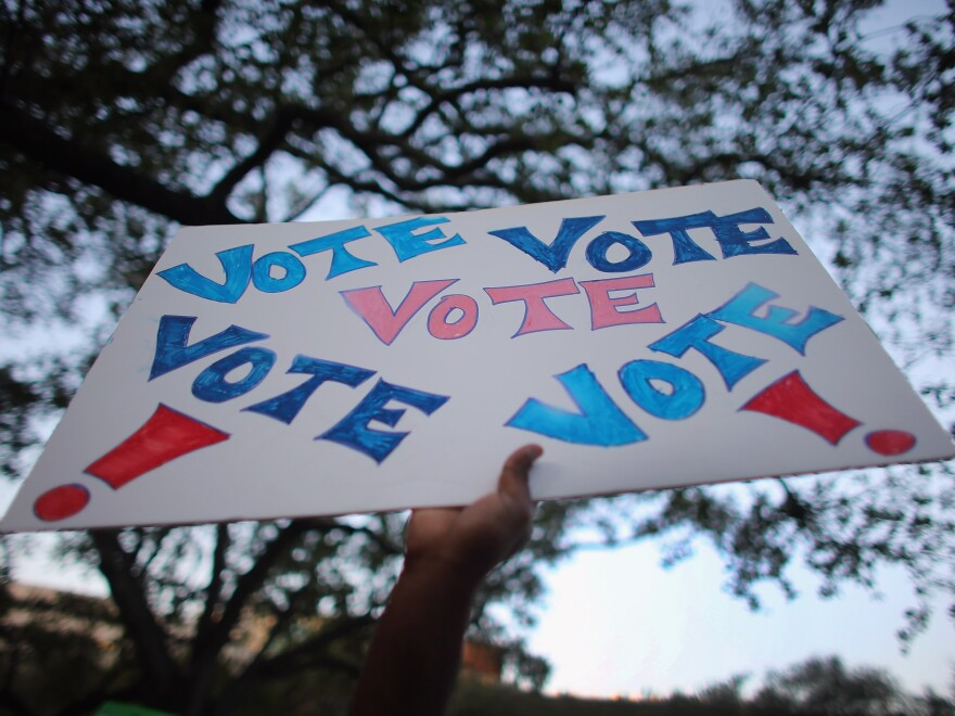 """A sign reading """"Vote"""" is held up during a rally for President Obama on Oct. 27 in Miami, Fla."""