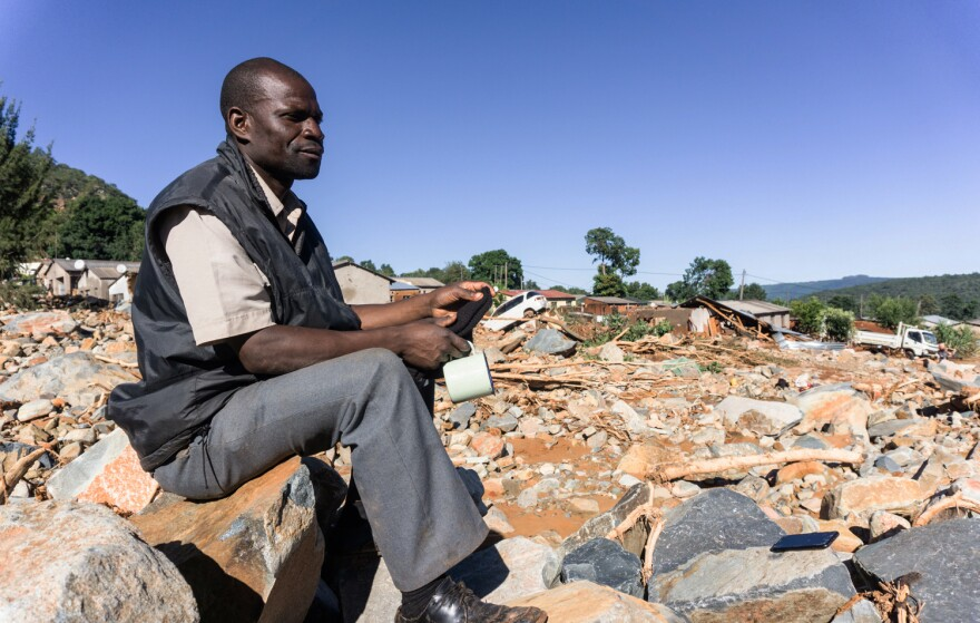 Moses Dudzai, 42, sits by an area where houses have been flattened by rocks falling from the mountain. His 19-month-old daughter has been missing since the storm and the landslide it triggered.