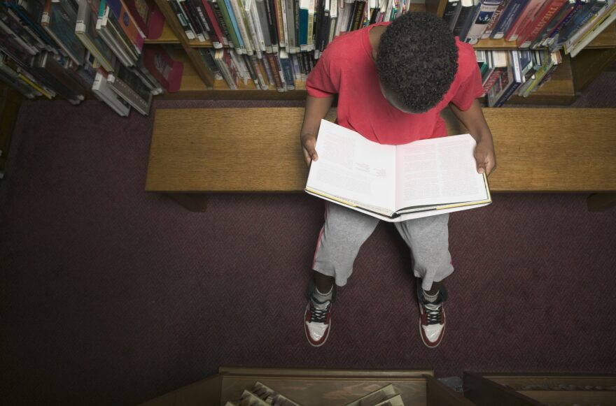 A young boy reading a book in a library. (Getty Images)