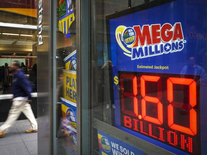A man walks past a newsstand with advertisements for the Mega Millions lottery on Tuesday. The $1.537 billion Mega Millions winning lottery ticket was sold in South Carolina.