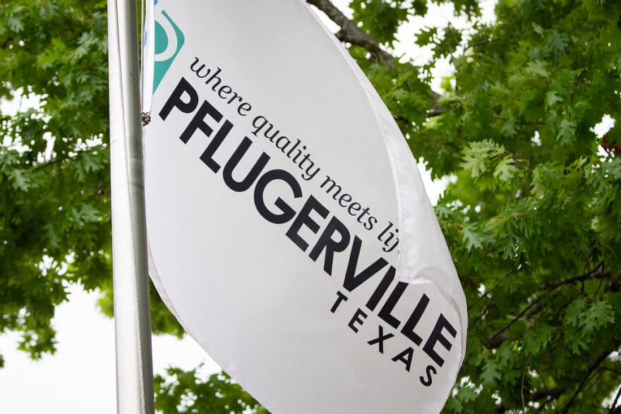 A Pflugerville flag flies outside the building housing City Council chambers downtown.