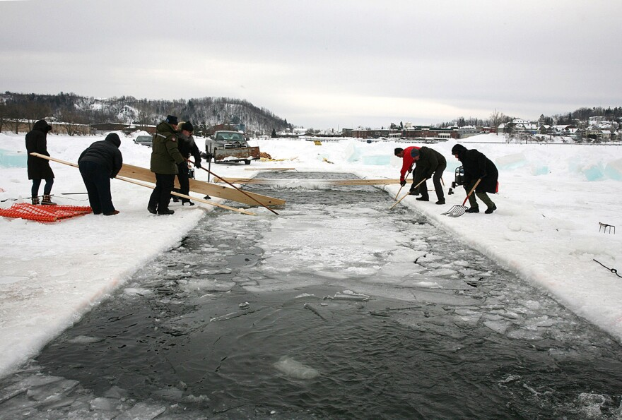 Volunteers clear ice from the swimming lanes before the start of the first Winter Swimming Championships in North America on Saturday in Newport, Vt., in Lake Memphremagog.