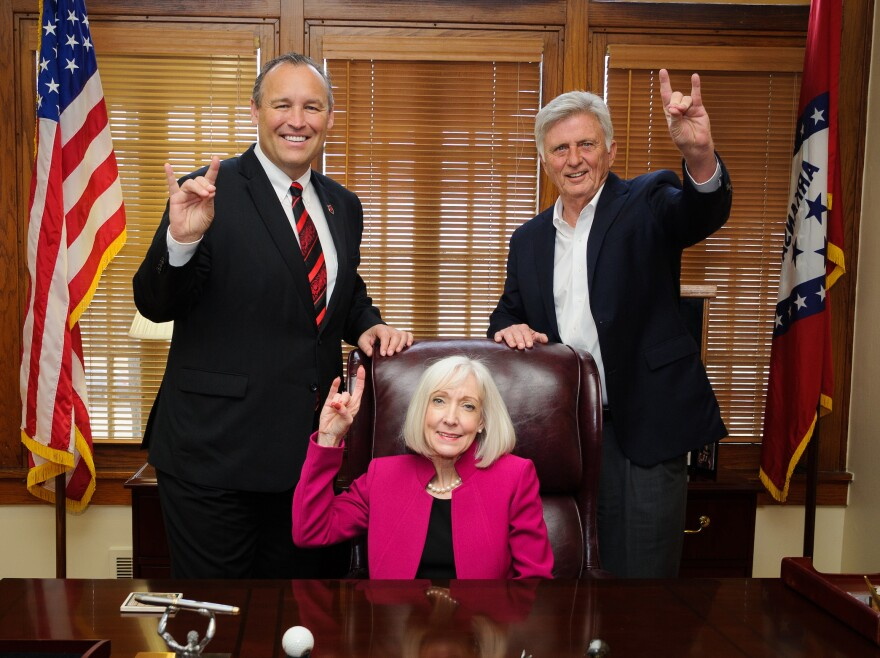 """Kays House Preview— (from left) Arkansas State University Chancellor Kelly Damphousse, former Arkansas first lady Ginger Beebe and former Arkansas Governor Mike Beebe give a """"Wolves Up"""" sign in the re-created governor's office at the restored Kays House."""