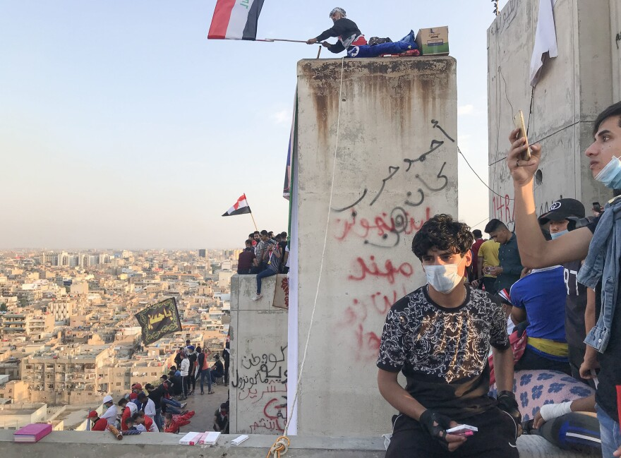 Demonstrators in Baghdad perch on top of an abandoned high-rise overlooking Tahrir Square.