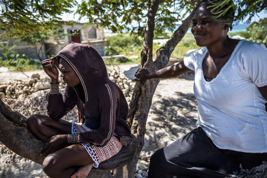 Remy Magene Dasny, 22, sits with her mother Berthenid Dasny. Remy had to stop attending school, where she is working on an accounting degree, because of safety concerns due to the unrest in Port-au-Prince.
