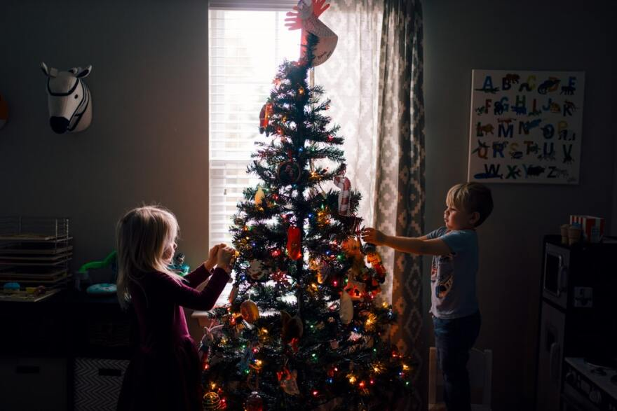 A young girl and boy decorate a Christmas tree with ornaments at home.