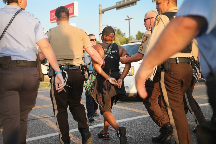 Police arrest a woman in Ferguson, Mo., protesting the shooting death of Michael Brown. Most officers in Ferguson and nearby Jennings are white, but the neighborhoods they police are predominantly African-American.