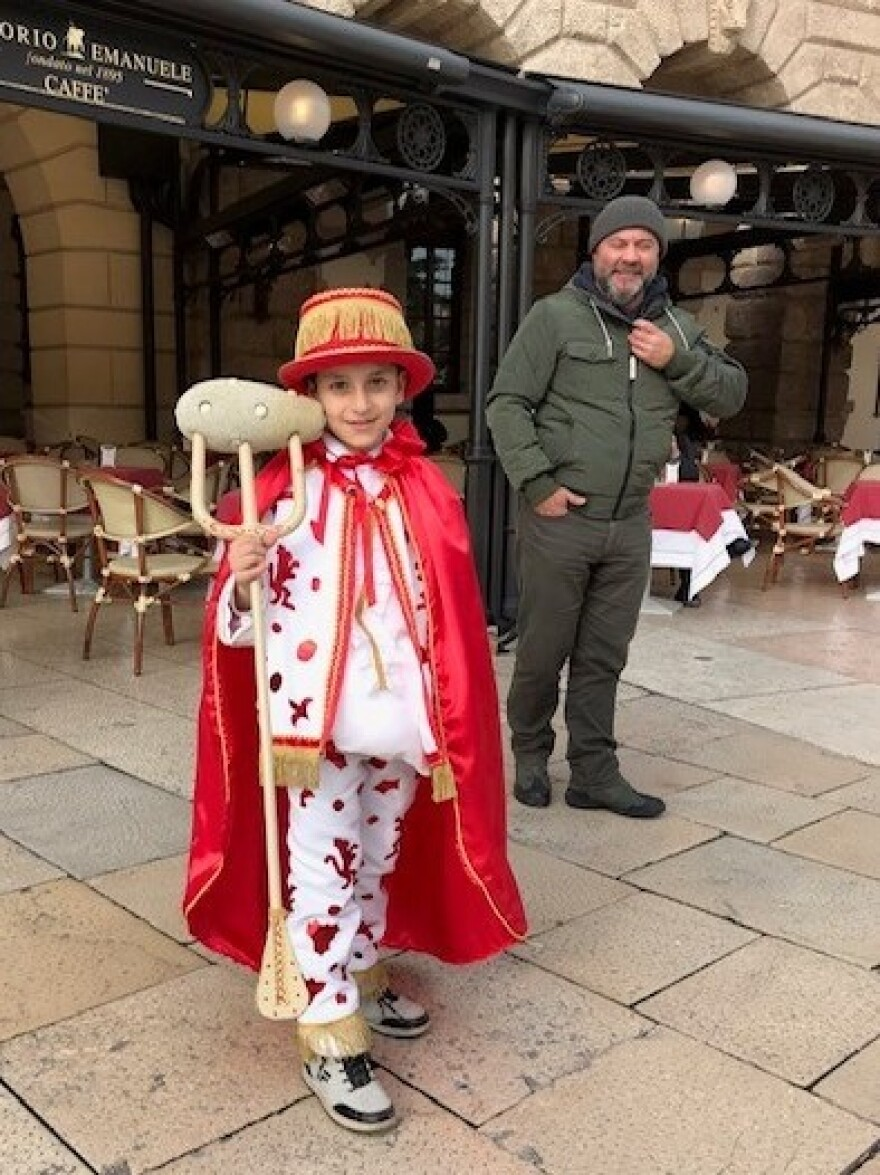 A young boy shows his spirit by dressing up as Papà del Gnoco and wielding an oversize fork spearing a giant piece of gnocchi.