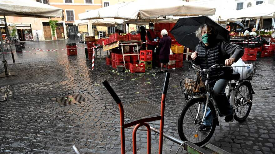 Nearly 49,000 people have now recovered from COVID-19 in Italy, which is reporting its first overall drop in positive cases since February. Here, a woman gets on her bicycle after shopping in Rome.