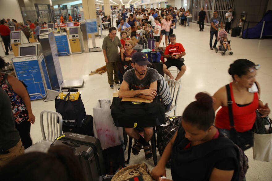 Edgar Algarin (center) and others wait in line to get a flight at the Luis Muñoz Marín International Airport in San Juan, Puerto Rico, on Monday. Hurricane Maria has left the island without power and with dwindling supplies of food and fuel.