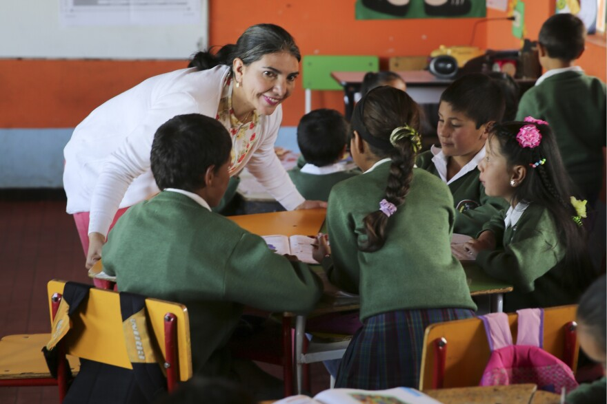 Teacher Maria Isabel Camango Guido instructs a group of students. Concepts from different subjects are combined in each lesson, into a simplified version of project-based learning.