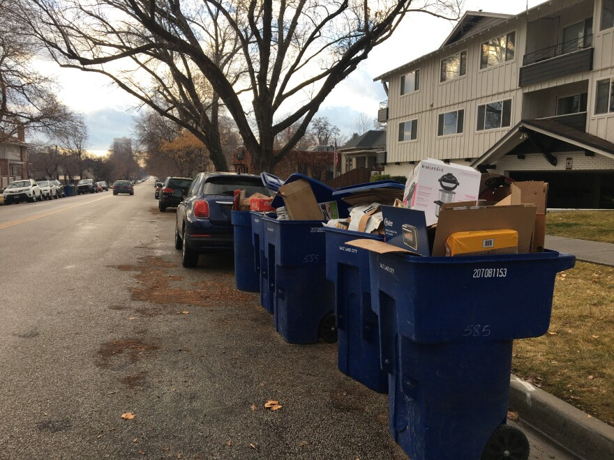 Photo of overflowing blue trash bins.