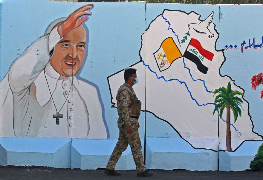 An Iraqi policeman walks by a mural depicting Pope Francis on the outer walls of Our Lady of Salvation Church in Baghdad on Monday. Pope Francis' visit from March 5 to 8 will include trips to Baghdad, the city of Mosul and a meeting with the country's top Shiite cleric Grand Ayatollah Ali al-Sistani.