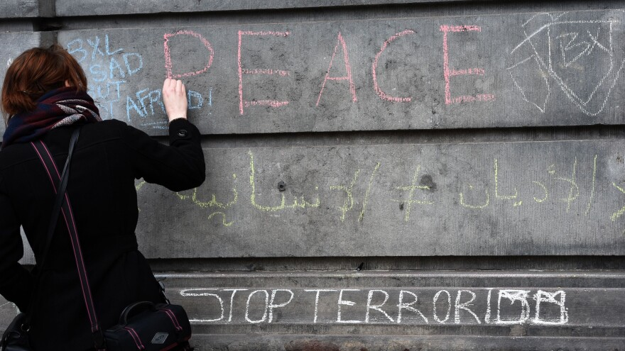 A woman writes a message on a wall in tribute to victims in Brussels on Wednesday, a day after deadly explosions struck the Belgian capital.