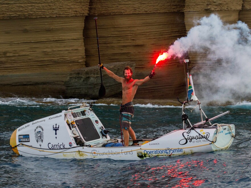 Chris Bertish enters the English Harbour at Antigua on Thursday, a flare trailing behind him in celebration. He paddled more than 4,050 nautical miles to reach this point.