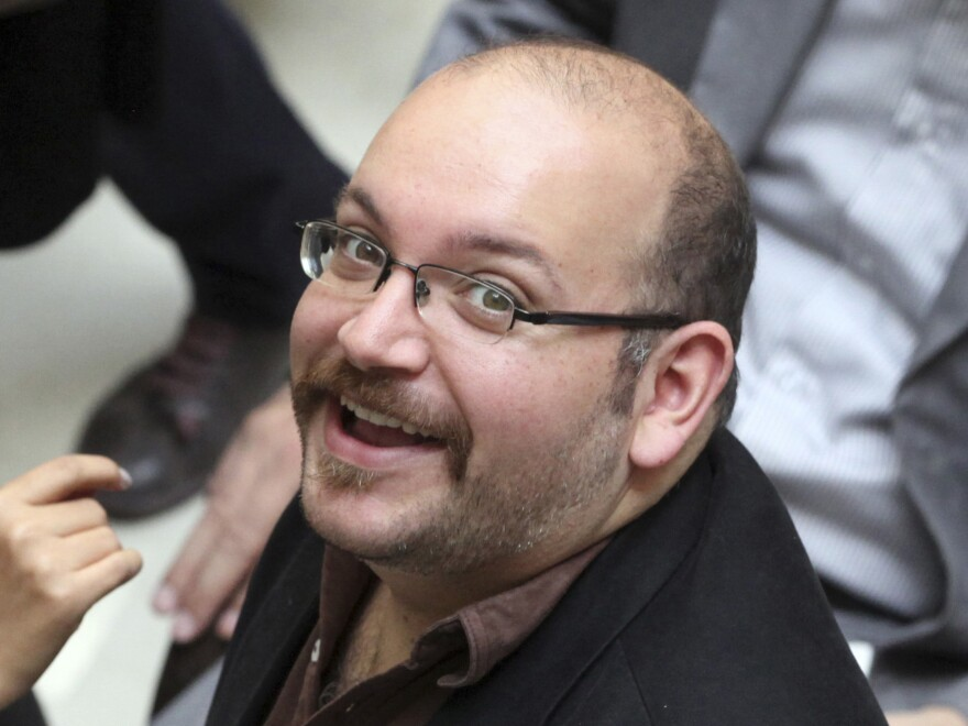Jason Rezaian, an Iranian-American correspondent for The Washington Post, smiles as he attends a presidential campaign even for President Hassan Rouhani in Tehran in 2013. Rezaian, who was arrested in July, was charged by Iran on Saturday.