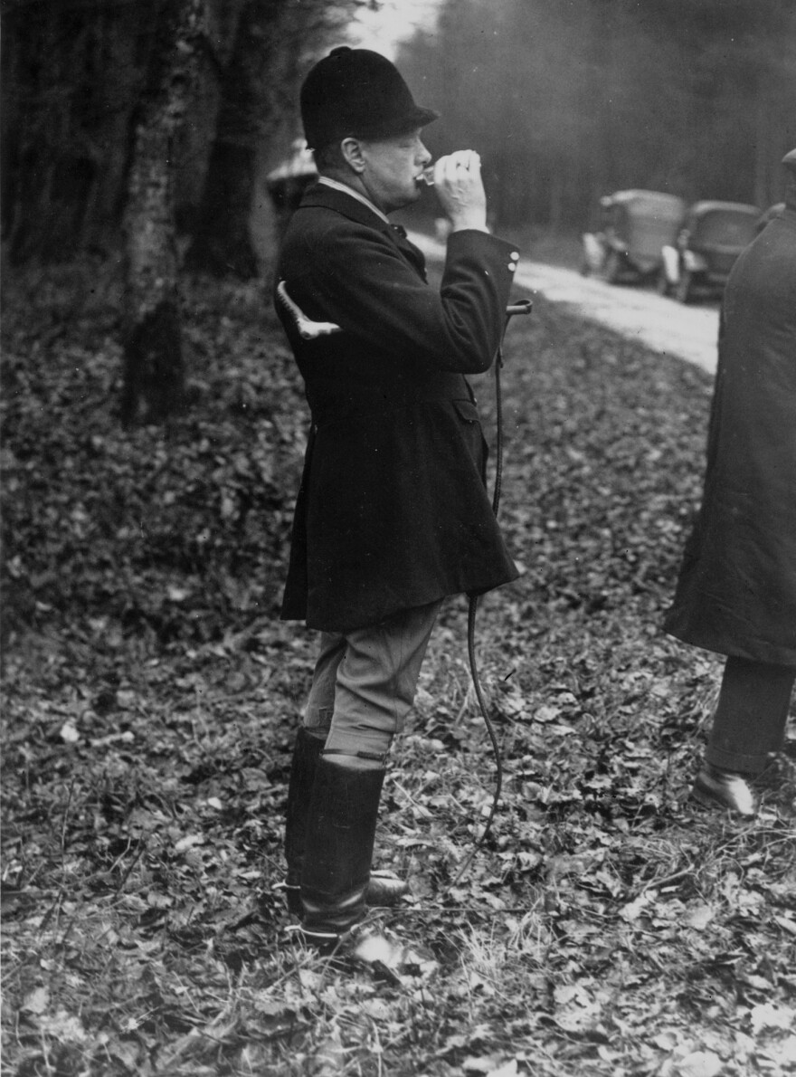 Churchill was known for starting the day with whisky. Here, whip in hand, he takes a nip at his hip flask at the start of a wild boar hunt in France, January 1927.