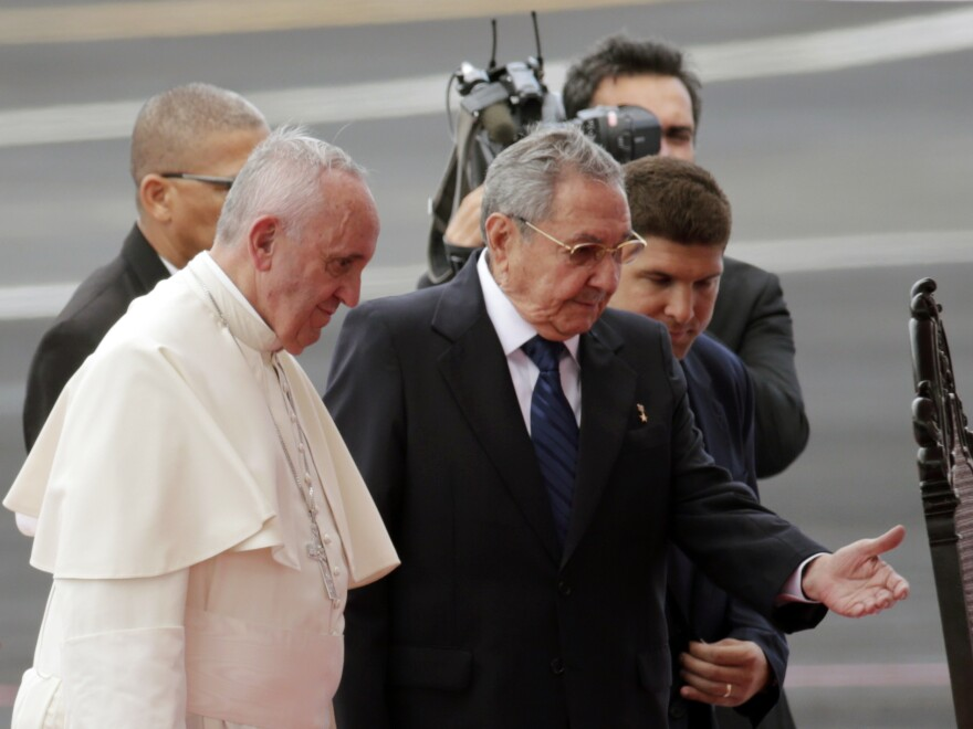 Pope Francis is escorted to a chair by Cuba's President Raul Castro during his arrival ceremony at the airport in Havana, Cuba, on Saturday.