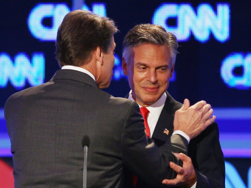 """<p>Former Utah Gov. Jon Huntsman (right) and Texas Gov. Rick Perry confer during a break in the Sept. 12 presidential debate in Tampa. Huntsman first objected to Perry's use of the word """"treasonous"""" then later used it himself. </p>"""