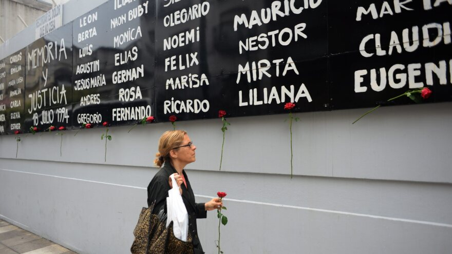 A woman leaves a rose in front of the AMIA Jewish community center facilities in Buenos Aires Monday, after Argentine prosecutor Alberto Nisman was found dead. Nisman had been investigating a 1994 bombing at the center.