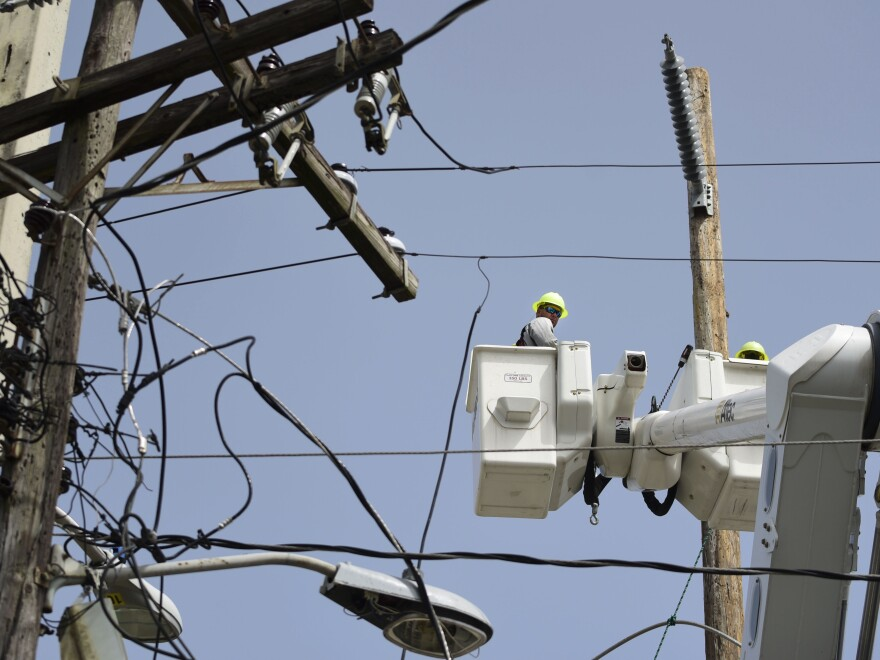 A lineman from the Electric Power Authority repairs distribution lines damaged by Hurricane Maria in Puerto Rico.