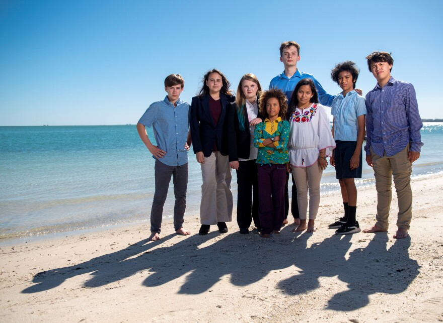 Eight Florida youths standing together on a beach.